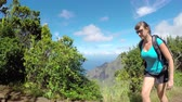 green canyon : Sportswoman walking on the edge of high mountain ridge overlooking vast jungle valley and blue ocean bay. Young woman on summer vacation hiking in Hawaiian mountains on a dirt path with stunning view