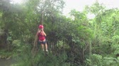 zamek błyskawiczny : Young happy woman sliding back and forth on high speed zipline rope above beautiful tropic deciduous forest. Girl having fun riding cable zipline above stunning lush tropical rainforest Wideo