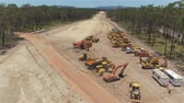 paver : AERIAL, MOVING FORWARD: Flying close above rocky heavy industry construction site zone and constructing machinery. Building multilane highway surrounded by stunning wild vast green lush forest