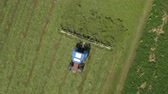 fieldwork : AERIAL, CLOSE UP: Flying above the farming tractor flipping mowed hay with rakes on agricultural farmland. Farmer speeding up hay drying by turning harvested hay around with a tractor-pulled tedder. Stock Footage
