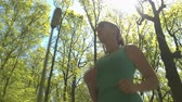 jogger : CLOSE UP, LOW ANGLE VIEW: Happy cheerful young woman runner jogging through big vast park on beautiful sunny spring day. Joyful athlete youthful girl running through tree avenue in stunning forest Stock Footage