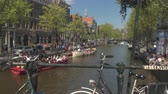excursão : AMSTERDAM, NETHERLANDS - 7th MAY 2016: Crowded Amsterdam river canals on busy Saturday, people enjoying sunny afternoon hanging on riverbanks and tourists cruising the canals on boat ride tours