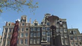 ЮНЕСКО : CLOSE UP: Gorgeous 17th century slim and high canal houses along Amsterdam waterway opened as museums, offices and hotels. Famous buildings with historic facades, skinny profile and grand gables