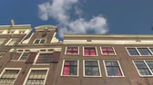 низким углом зрения : LOW ANGLE VIEW, CLOSE UP: Gorgeous 17th century slim and high canal houses with historic facades and grand gables. Famous buildings along Amsterdam waterway opened as museums, offices and hotels