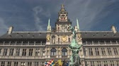 spravedlnost : CLOSE UP, LOW ANGLE VIEW: Brabo statue fountain in front of stunning famous City Hall richly ornamented building, Antwerp, Belgium. Fascinating historic architecture on Great Market square in Antwerp