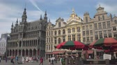 сувениры : BRUSSELS, BELGIUM - 10th MAY 2016: Crowded busy central square, Grand Place. Tourists sightseeing, mingling and buying souvenirs in front of gothic architecture style guildhall City of Brussels Стоковые видеозаписи