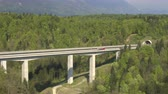 поднятый : AERIAL: Cars and semi trucks speeding along the multiple lane highway viaduct and driving into and out of the tunnel under the mountain Стоковые видеозаписи
