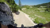 terreno extremo : POV FIRST PERSON VIEW: Extreme biker riding downhill along the singletrack bandah rocky track and skinny wooden trails in mountain bike park. Beginner cyclist biking on the easy bikepark flow trail. Vídeos