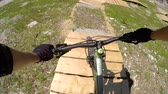 крайняя местности : POV FIRST PERSON VIEW: Extreme biker riding downhill along the singletrack bandah rocky track and skinny wooden trails in mountain bike park. Beginner cyclist biking on the easy bikepark flow trail. Стоковые видеозаписи