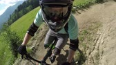 крайняя местности : PORTRAIT CLOSE UP: Extreme biker riding downhill e-bike on singletrack bandah track and skinny wooden trails in mountain bike park. Beginner cyclist biking electric bicycle on easy bikepark flow trail Стоковые видеозаписи