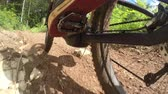 ciclismo : CLOSE UP: Unrecognizable downhill biker riding e-bike on dirt trail through the forest terrain. Freeride biker pedaling electric bicycle along the offroad track through green woods in sunny summer Stock Footage
