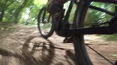 terreno extremo : CLOSE UP: Unrecognizable downhill biker riding e-bike on dirt trail through the forest terrain. Freeride biker pedaling electric bicycle along the offroad track through green woods in sunny summer Stock Footage