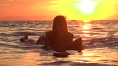 surfista : SLOW MOTION, CLOSE UP: Young happy woman paddling out on surf in deep ocean water at beautiful golden sunset. Girl relaxing on surfboard and enjoying her vacation on dreamy Zanzibar, Tanzania