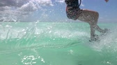 kiting : SLOW MOTION: Young surfer girl kiteboarding and turning, splashing the water drops on beautiful blue ocean surface. Cheerful kiter woman kitesurfing in amazing turquoise lagoon of exotic island Stock Footage