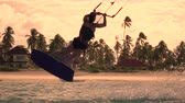 kiting : SLOW MOTION: Young kiter girl kitesurf jumping trick in sunny morning. Extreme kiteboarder woman kiting and jumping rally in beautiful blue lagoon on summer vacation at sunset golden light.