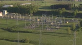 pylon : AERIAL: Flying above industrial facility with power line towers and power plant generator transmitting and distributing electrical energy and power in beautiful lush green surroundings