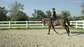 rancho : SLOW MOTION CLOSE UP: Beautiful big dark brown gelding cantering in sandy manege. Dressage female rider horseback riding a strong powerful brown stallion horse, galloping in outdoors riding arena