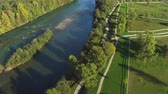 организованный : AERIAL: Flying above wide river running by big beautiful park with recreational footpaths for long walks and jogging, barbecue area, green equestrian pasture fields and outdoors riding arenas