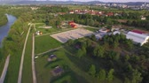 riding arena : AERIAL: Flying above wide river running by big beautiful park with recreational footpaths for long walks and jogging, barbecue area, green equestrian pasture fields and outdoors riding arenas
