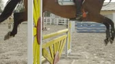 amazona : SLOW MOTION CLOSE UP: Unrecognizable horsewoman horseback riding strong brown horse showjumping over fences in sandy parkour dressage arena. Competitive rider training jumping over obstacles in manege