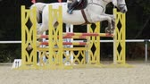 competere : SLOW MOTION, CLOSE UP: Beautiful grey horse jumping over fence and performing in competitive jumping event in outdoors sandy parkour riding arena. Unrecognizable person riding powerful gelding