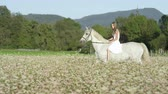 klusat : SLOW MOTION CLOSE UP DOF: Beautiful girl in white dress bareback riding stunning grey horse through dense pink flowering field. Pretty young happy girl on ride with mighty white stallion in nature