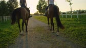 horsemanship : SLOW MOTION, CLOSE UP: Two young girls horseback riding amazing strong brown stallions walking into magical golden sunset on beautiful horse ranch farm. Girlfriends on relaxing morning ride at sunrise Stock Footage