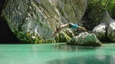 watercourse : SLOW MOTION CLOSE UP: Happy young man jumping headfirst into water off a big rock in the middle of freezing cold and beautiful green Soca river. Cheerful guy diving into refreshing riverbed head first Stock Footage