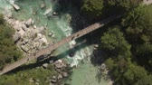 emeraude : AERIAL: Two mountain bikers crossing wooden bridge over beautiful emerald river running through green forest.   Raging whitewater rapids and clear mountain stream flows between rocks in rocky riverbed
