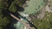 riverbank : AERIAL: Flying above big beautiful wooden rope bridge leading over stunning emerald mountain river stream. Clear raging whitewater rapids running fast between big sharp rocks in rocky riverbed Stock Footage