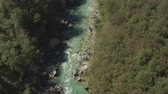 vor : AERIAL: Flying above professional sportsmen kayaking fast between sharp rocks in riverbed. Dangerous rapids and white water mountain river running through beautiful lush forest on stunning summer day