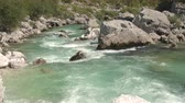 riverbank : AERIAL CLOSE UP: Flying close above amazingly fast current of crystal clear Soca river flowing in rocky riverbed. Furious white water running between big sharp rocks in beautiful and wild landscape Stock Footage