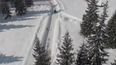 домик : AERIAL: Turquoise sport car driving on slippery frosty street past traditional alpine chalet in dreamy ski resort. Picturesque mountain valley and vast conifer forest on beautiful sunny winter day