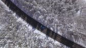 snow covered spruce : AERIAL: Flying above turquoise sport car driving on narrow highway through deep snowy woods on sunny winter day. Amazing road trip through picturesque nature in rural countryside in magical wintertime