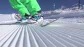 on piste : SLOW MOTION CLOSE UP: Extreme snowboarder riding and carving past the camera on perfectly groomed snow in sunny mountain ski resort. Unrecognizable boarder having fun snowboarding in snowy mountain Stock Footage