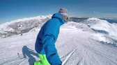 スキーヤー : SELFIE: Happy snowboarder snowboarding down the ski slope, turning and speeding in perfectly groomed mountain ski resort. Young snowboarder having fun riding in snowy winter.