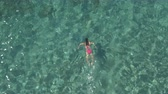 kurbağa : AERIAL: Attractive young woman coming for air, submerging and swimming underwater in crystal clear transparent turquoise ocean. Sunlight penetrating water surface revealing stones, sand on sea bottom Stok Video