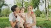 tossing up : SLOW MOTION, CLOSE UP, DOF: Happy young daddy playing with cheerful baby girl on his lap, tossing her up and down on stunning sunny day. Beautiful joyful mother sitting besides on blanket and smiling Stock Footage
