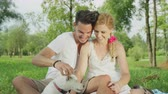 tranças : SLOW MOTION, CLOSE UP, DOF: Beautiful blonde Caucasian woman and dark haired man sitting on soft blanket in green Central park, cuddling and scratching small adorable dog running around having fun