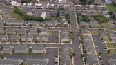 припаркован : AERIAL: Flying above rooftops of perfectly identical twin houses with big parking lots and colorful linked rowhouses standing along busy highway crowded with vehicles in fancy residential neighborhood Стоковые видеозаписи