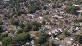 припаркован : AERIAL: Flying above exclusive upper class houses with gardens and private driveways and luxury low raise apartment buildings in beautiful modern overgrown with trees suburban town on sunny day