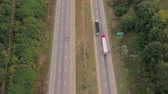 turnpike : AERIAL: Flying above busy multilane interstate motorway crowded with speeding vehicles. Empty and lighter semi truck overtaking in a hurry a trade trailer truck loaded with cargo shipping the freight