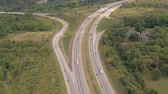 turnpike : AERIAL: Flying above busy multilane interstate highway crowded with speeding vehicles. Personal cars commuting and traveling on holidays, semi trucks and trade trailers shipping loaded cargo by day