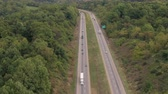 multilane : AERIAL: Flying above busy multilane interstate highway crowded with speeding vehicles. Personal cars commuting and traveling on holidays, semi trucks and trade trailers shipping loaded cargo by day