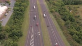 turnpike : AERIAL: Flying above busy multilane interstate speedway crowded with speeding vehicles. Personal cars commuting and traveling on holidays, semi trucks and trade trailers shipping loaded cargo by day