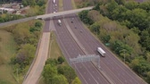 interestadual : AERIAL: Flying above busy multilane interstate motorway crowded with speeding vehicles. Personal cars commuting and traveling on holidays, semi trucks and trade trailers shipping loaded cargo by day
