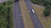 спидвей : AERIAL: Flying above busy multilane interstate highway crowded with speeding vehicles. Personal cars commuting and traveling on holidays, semi trucks and trade trailers shipping loaded cargo by day