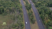 спидвей : AERIAL: Flying above busy multilane interstate expressway crowded with speeding vehicles. Personal cars commuting and traveling on holidays, semi trucks and trade trailers shipping loaded cargo by day