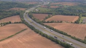 turnpike : AERIAL: Personal cars driving on multilane interstate highway, commuting and traveling on holidays. Semi trucks and trade trailers shipping loaded cargo, traveling through rural landscape on sunny day Stock Footage