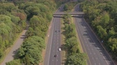 turnpike : AERIAL: Flying above overpass bridge and underpass multilane interstate expressway. Speeding vehicles, personal cars commuting, people traveling on holidays, semi trucks loaded with cargo shipping
